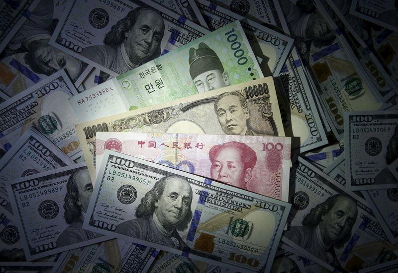 © Reuters. Южнокорейский вон, китайский юань и японская иена рядом с купюрой в 100 долларов.