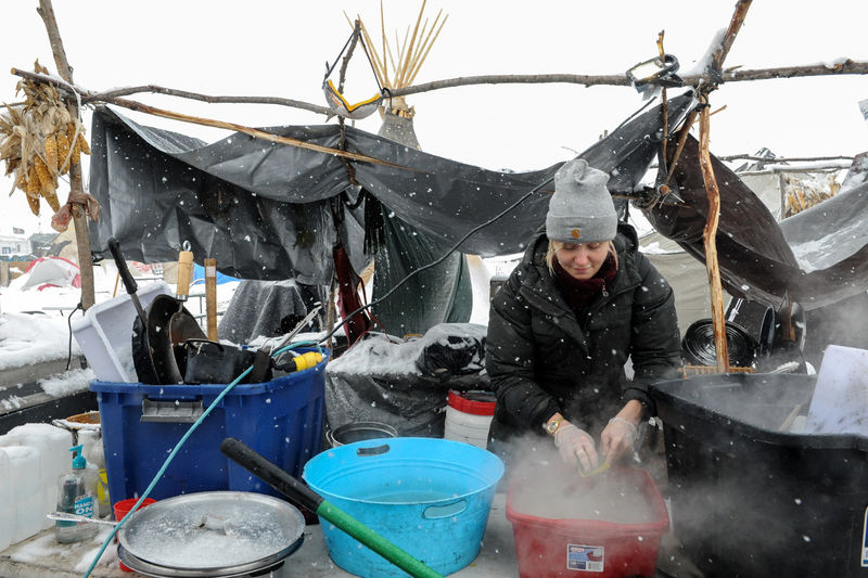 © Reuters. A woman washes dishes in the Oceti Sakowin camp in a snow storm during a protest against plans to pass the Dakota Access pipeline near the Standing Rock Indian Reservation, near Cannon Ball, North Dakota, U.S.