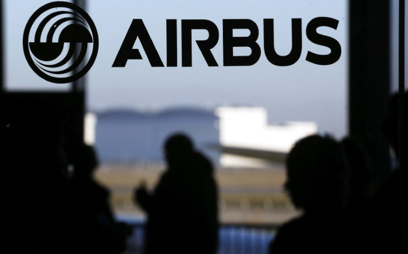 © Reuters. People are silhouetted past a logo of the Airbus Group during the Airbus annual news conference in Colomiers