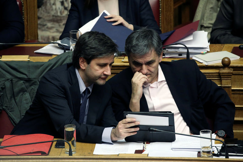 © Reuters. Greek Finance Minister Tsakalotos and Alternate Finance Minister Chouliarakis look at their notes during a parliamentary session before a budget vote in Athens