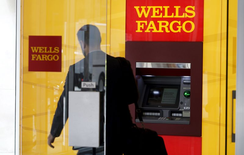 © Reuters. A man walks by a bank machine at the Wells Fargo & Co. bank in downtown Denver