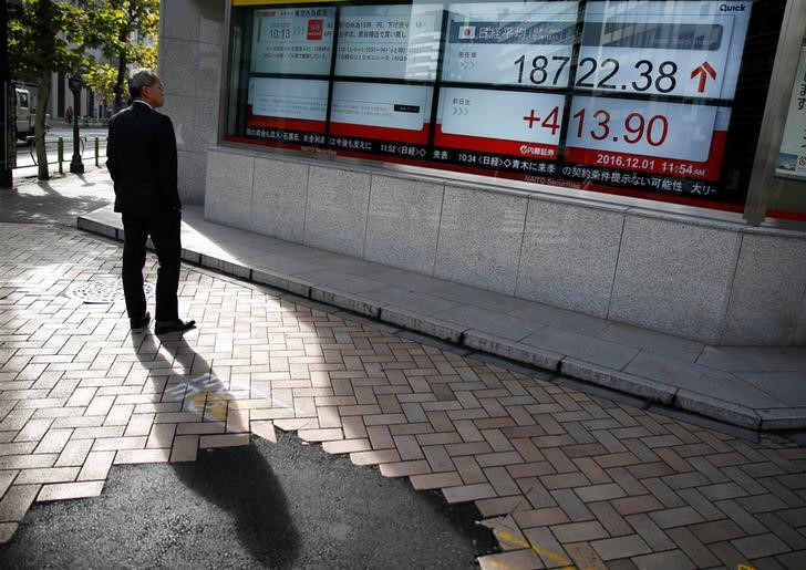 © Reuters. A man looks at an electronic board showing Japan's Nikkei average outside a brokerage in Tokyo