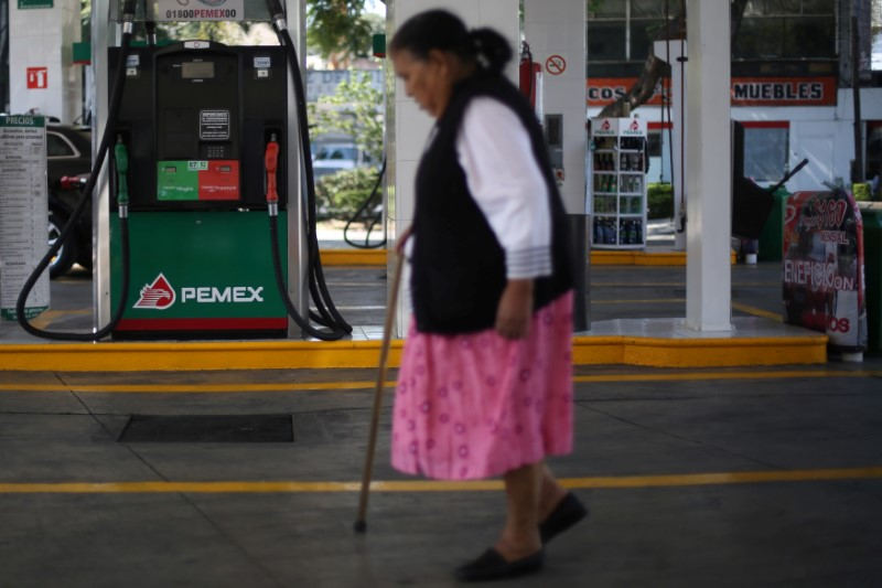 © Reuters. A woman walks next to fuel pumps at Pemex gas station in Mexico City