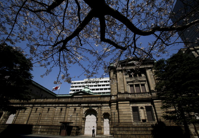 © Reuters. A security officer stands guard near half-blooming cherry blossoms, outside the Bank of Japan headquarters in Tokyo
